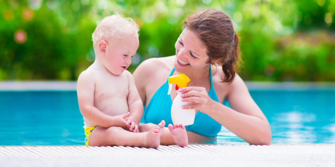 a mother applying sunscreen to her baby